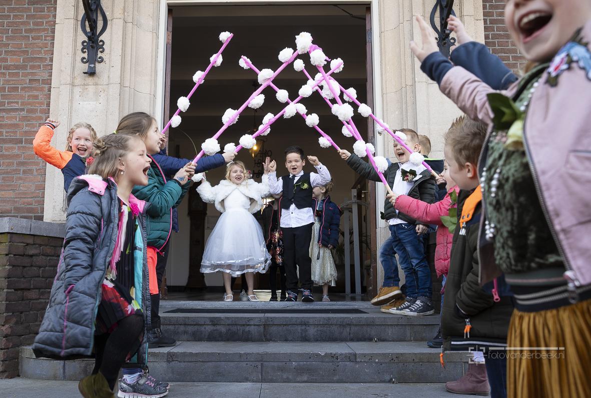 """Boaz Klaverstijn en Sylvie van Oene """"trouwden"""" in het gemeentehuis. Na het ja-woord verraste het verse bruidspaar iedereen met een heuse knuffel, een kusje durfden ze niet.... in het kader van project trouwen, groep 3 van de Parel uit Wapenveld, leerkracht is Margriet Riepma. Tel. school: 038 4478205. Hele klas speelde mee. Klasgenootjes speelden vaders en moeders, broertjes en zusjes van de bruid en bruidegom. Maar ze speelden ook voor getuigen, vrienden vriendinnen, bruidsmeisjes etc. Buitengewoon Ambtenaar van de Burgerlijke Stand Ditty Jagersma deed de ceremonie."""